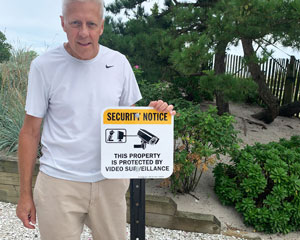 Property protected by remotely monitored security services sign